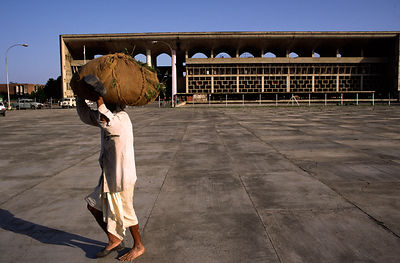 India - Chandigarh - A man carries a bundle past the Court building