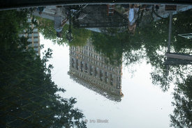 The Flatiron Building reflected in a pond at Madison Square Park. The Flatiron Building, originally the Fuller Building, is a triangular 22-story[4] steel-framed landmarked building located at 175 Fifth Avenue in NY.