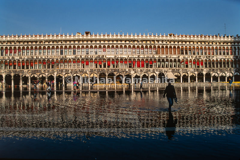 People trudge through the flooded area in front of the Procuratie in Piazza San Marco. Venice, Italy, 1993.