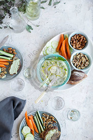 Meyer Lemon Basil Hummus served with vegetables, bread and white wine. Photographed on a white plaster background.