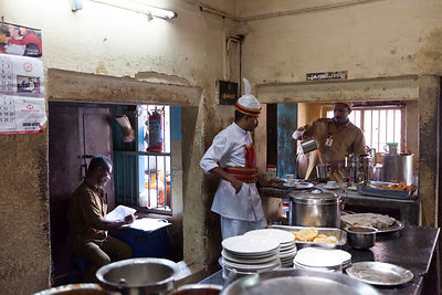 India - Kottayam - A waiter waits for tea to be poured for an order while the Supervisor checks the books in the kitchen of the Indian Coffee House
