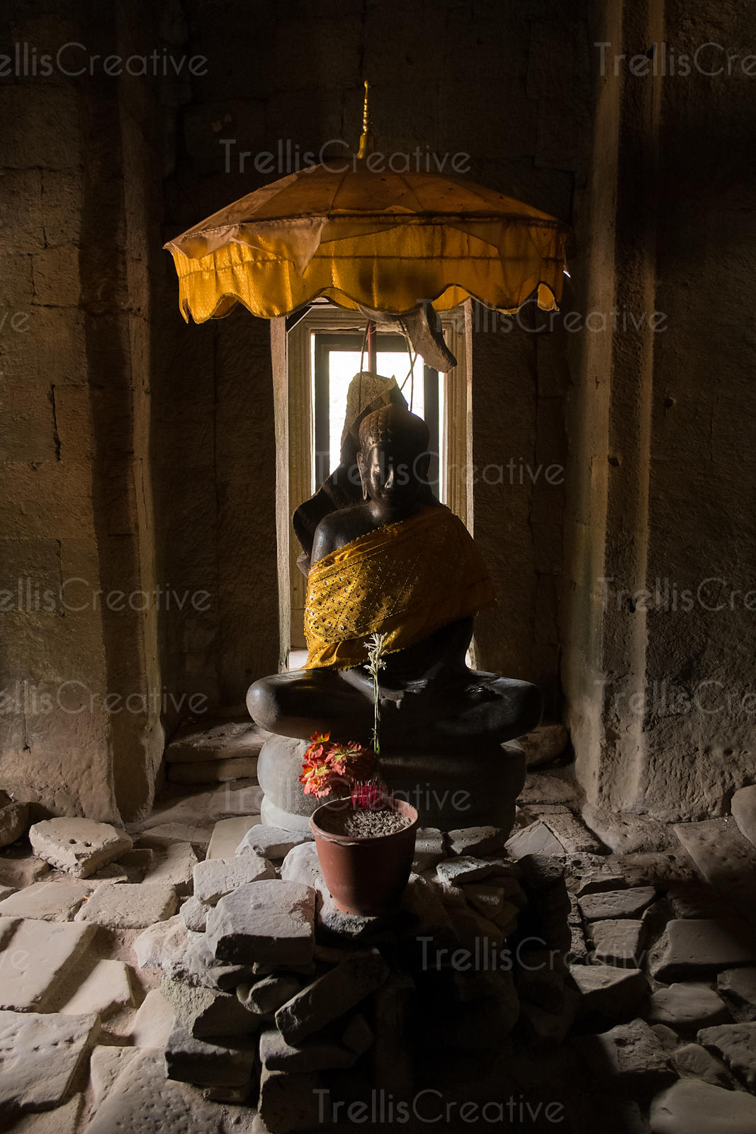 Incense and offerings in front of a Buddah statue in Angkor Wat temple