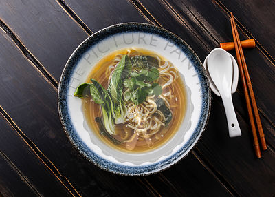 Ramen asian noodle in broth with pak choi cabbage in bowl on dark wooden background