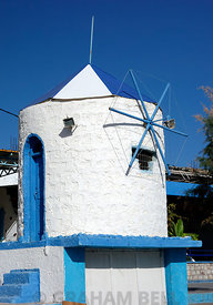 Small windmill besides the beach, Stegna, Archangelos, Rhodes, Dodecanese Islands, Greece.