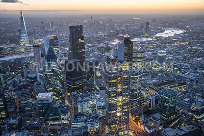 Dusk aerial view over the City of London. Heron Tower / Sales Force Tower, Swiss Re Tower, The Leadenhall Building, The Shard, skyscrapers of London. England, UK .Aerial view .