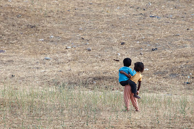 A girl carries her younger brother across a field in Pushkar, Rajasthan, India