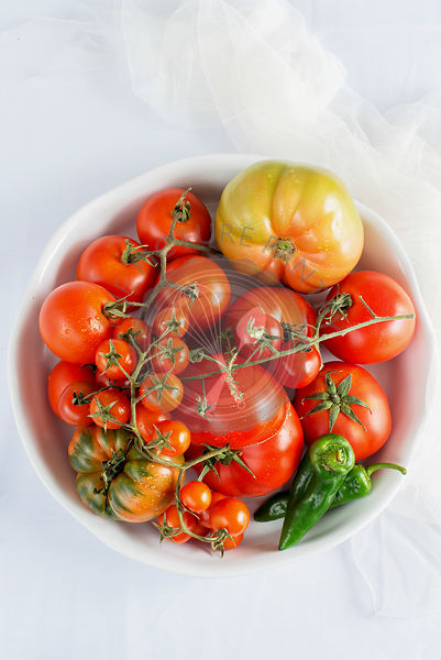 Tomatoes and green chilli in a white bowl