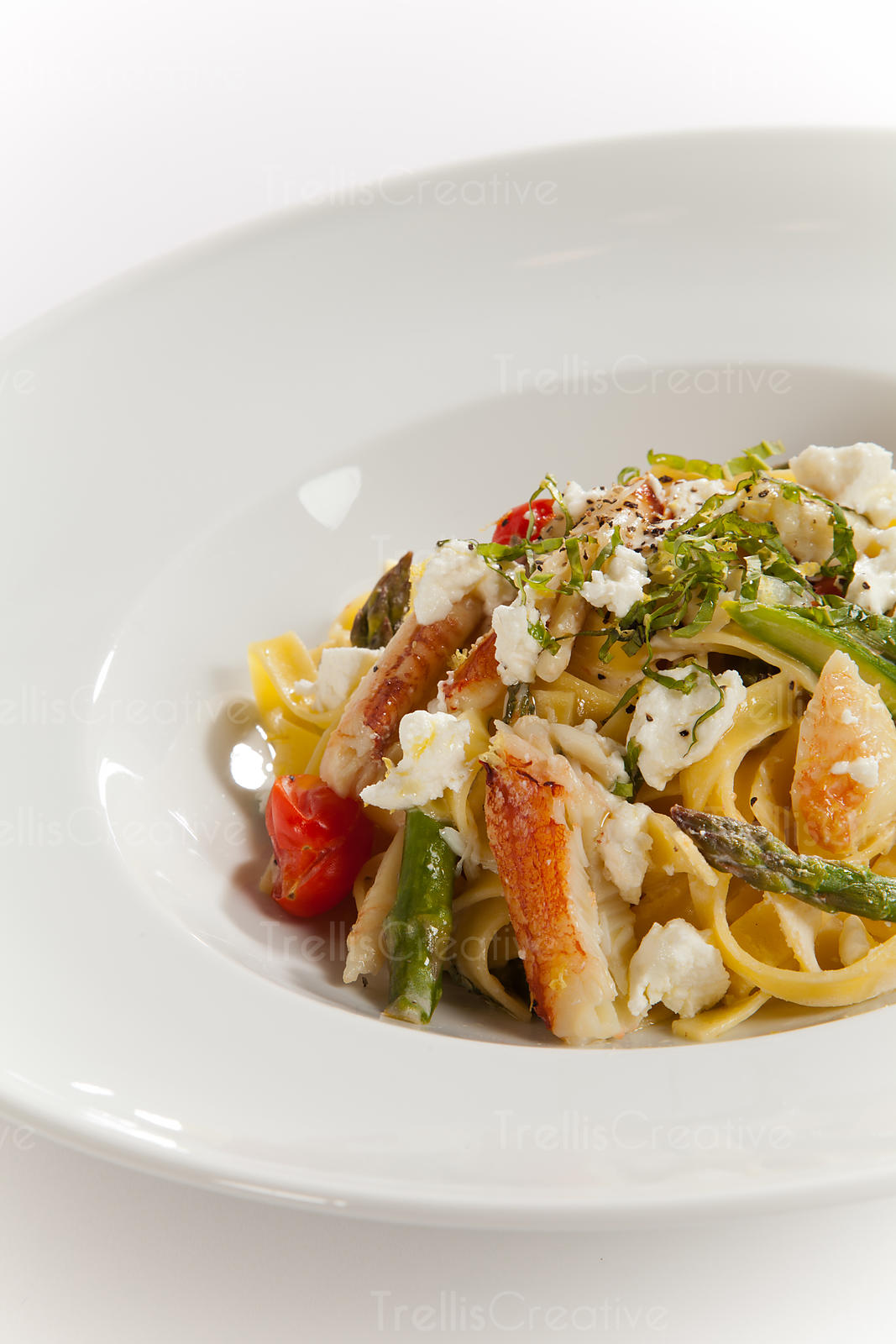 A bowl of linguini topped with crab meat, goat cheese and vegetables