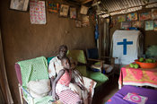 Grandmother with grandchildren in their home. Kenya.