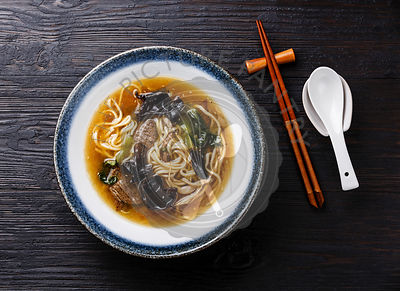 Asian wheat Ramen noodle with beef, wood mushroom and bok choy cabbage in bowl on dark wooden background