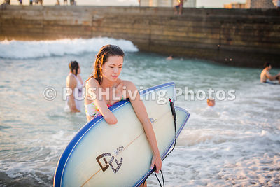 Young woman with her surfboard on Waikiki Beach