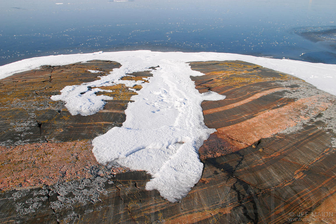 Evaporating snow on rock by frozen ice sea