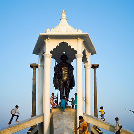 Children play on a statue of Gandhi on the beach at Pondicherry, India