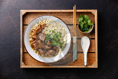 Slow cooked Beef meat with Asian noodles in broth in wooden tray on dark background