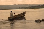Man in evening light rowing boat along river Nile at its source, Lake Victoria, in Uganda Africa