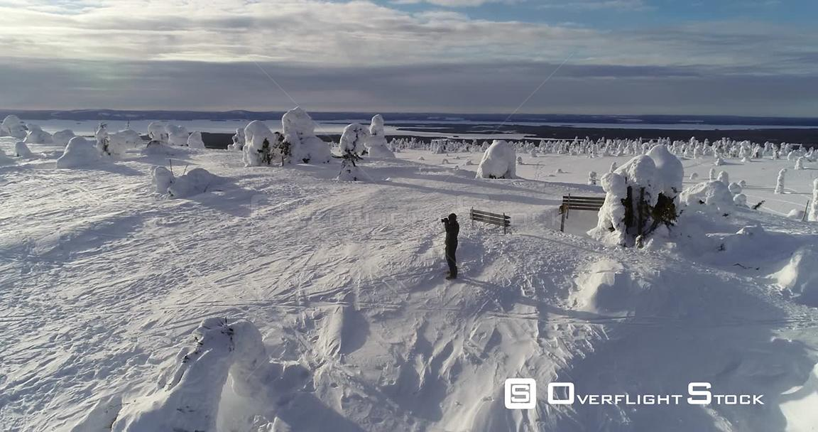 Hiking, Snowy Mountain, 4k Aerial View Around a Man Taking Pictures on the Top of a Fjeld Tunturi, Full of Snow Covered Trees, Riisitunturi National Park, Lapland, Finland