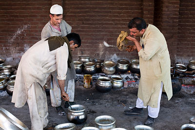 India - Srinagar - Khan Mohammed Sharief Waza, a traditional Kashmiri chef inspects and tastes dishes at a Wazwan, a Kashmiri feast