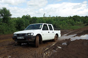 White Isuzu four wheel drive jeep driving on muddy road Kenya Africa