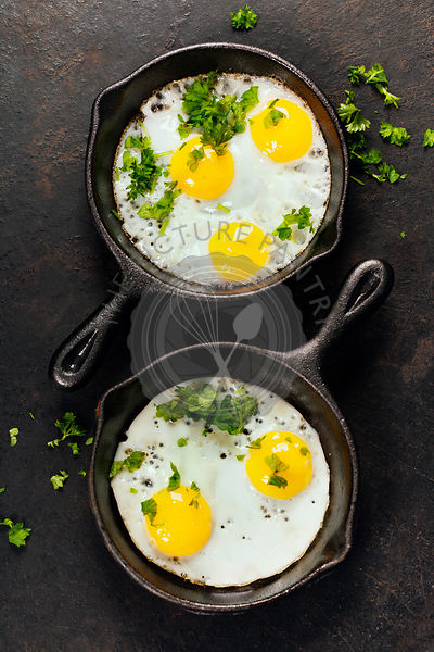 Pans with fried eggs and herbs on old metal background, top view. Food. Breakfast. Healthy food.