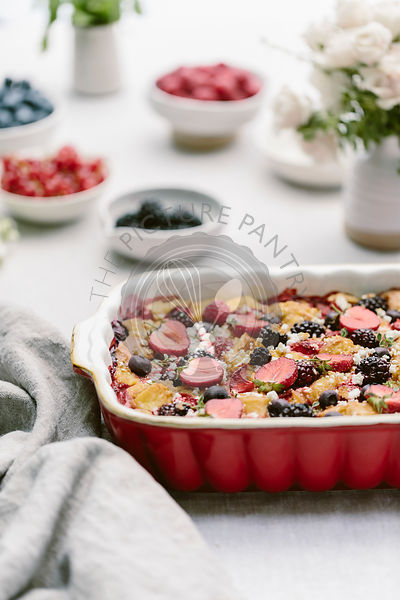A goat cheese & berry bread pudding is photographed from the front after it was baked.
