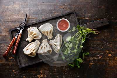 Georgian dumplings Khinkali with meat and tomato spicy sauce on cutting board