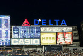 Spectators and night signage on a full moon night at the Yankee Stadium in Bronx, NYC.