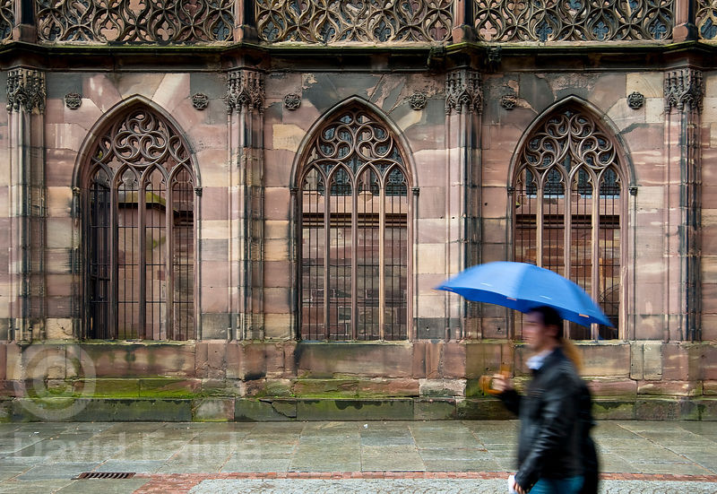 A couple walk in the rain in front of the Cathedral of Our Lady of Strasbourg (French: Cathédrale Notre-Dame-de-Strasbourg, German: Liebfrauenmünster zu Straßburg)