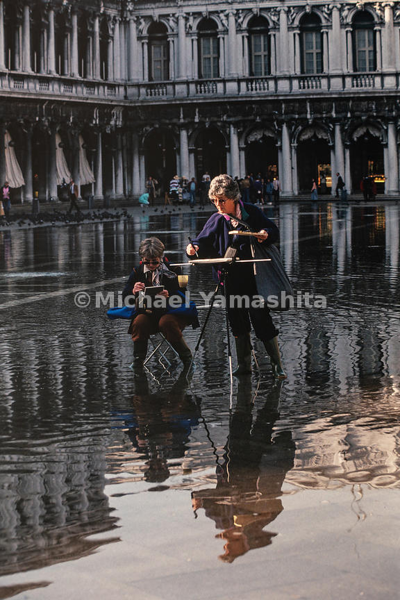 Artists sketch in front of Piazza San Marco regardless of the acqua alta that occurs in the Veneto region. Venice, Italy, October, 1993.