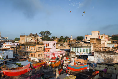 Early light on Pushkar with women folding laundry on a roof and hot air balloons in the sky, Rajasthan, India