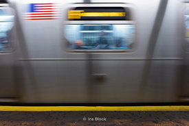 A moving F train at the 23rd station in Manhattan, NY.