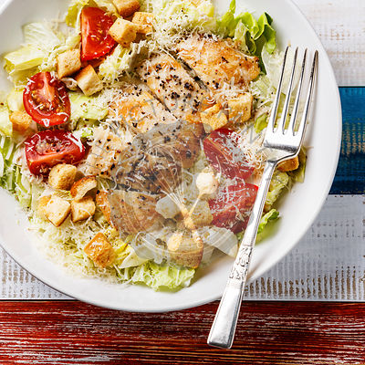 Caesar salad with chicken breast and fork close-up