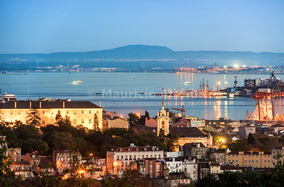 Alcântara district and the Tagus river. The Arrábida mountain range on the background, at dusk. Lisbon, Portugal