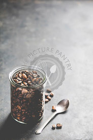 Coffee composition on dark background. Coffee beans in glass jar. Copyspace