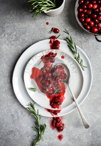 A rustic homemade cranberry suace spooned across a stack of plates with fresh rosemary and cranberries throughout the frame.