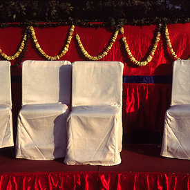 A stage set for a wedding with chairs and garlands, New Delhi, India