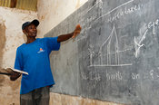 Teacher teaching science on a blackboard in a classroom, Kenya