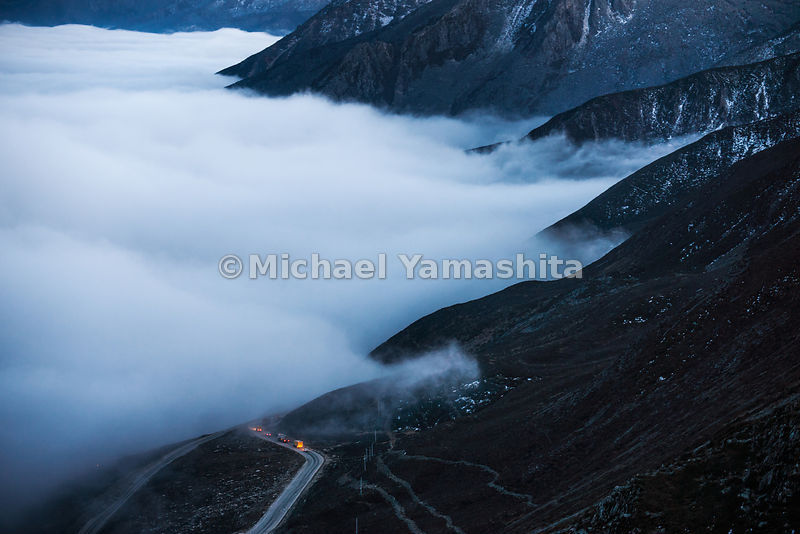 Zeduo Pass, the gateway to Tibet from wetsern China, at 14,100 ft (4298 m) was once traversed by mule and horse caravans, but now trucks push on through the mist en route to Kanding.