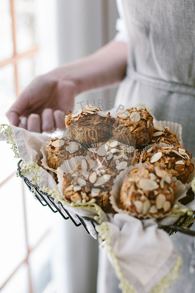 A woman is photographed from the front view as she was holding freshly baked parsnip morning glory muffins.