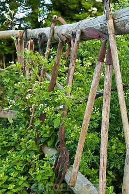Fence decorated with old garden tools. Midney Gardens, Midney, Somerton, Somerset, UK