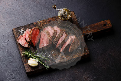 Sliced tenderloin Steak Roast beef on wooden cutting board on dark background
