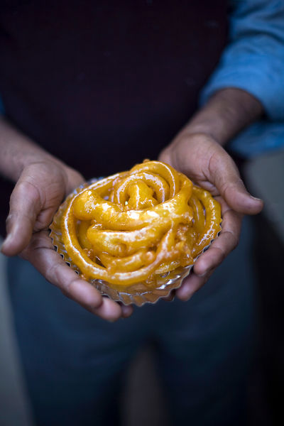 India - Delhi - A man holds jalebis at the Old & Famous Jalebi Wala