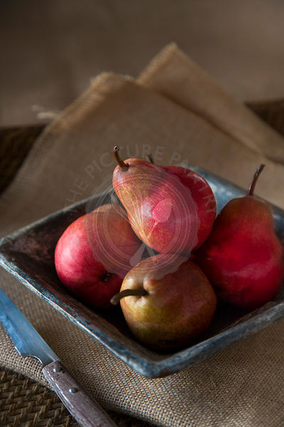 group of red pears in rustic ceramic dish, with knife, on sack cloth and woven tray.