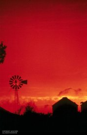 Windmill and barn aginst red sky