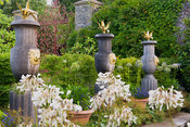 Carved oak urns with gilded lions' heads and topped with gilded agaves line the rill in the Collector Earl's Garden designed by Julian and Isabel Bannerman. Arundel Castle Gardens, Arundel, West Sussex, UK