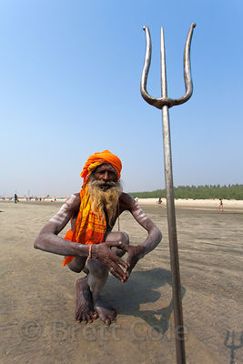 An elerly sadhu (holy man) does yoga at the Gangasagar Mela, a Hindu pilgrimage to Sagar Island in the Bay of Bengal in India, where the Ganges River meets the sea.