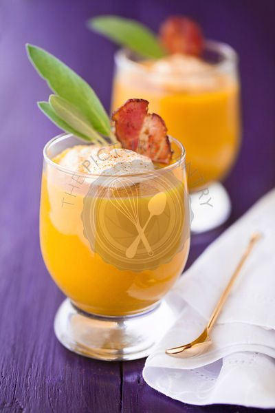Pumpkin soup served in glasses with whipped cream, bacon and sage