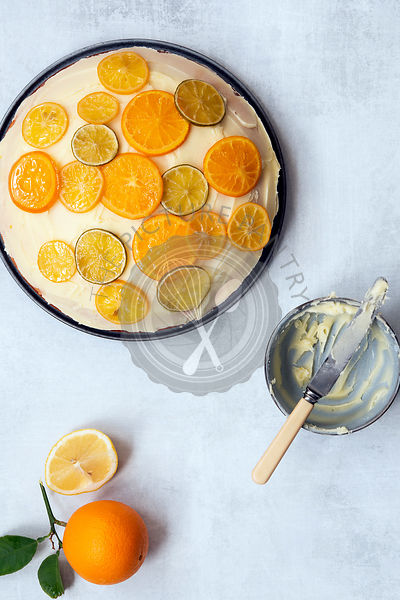 A round orange cake spread with butter icing and decorated with slices of candied lemon, lime and orange.