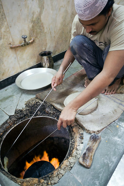 India - Delhi - L M Rahman preparing and cooking fresh naan bread in the tandoor oven at Karim's Restaurant