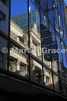 Facade of the stone building of the Central Bank of the Argentine Republic, Buenos Aires, Argentina, reflected in the glass of a modern office building