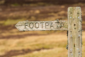 Lichen covered footpath sign on heather moorland, North Yorkshire, UK.